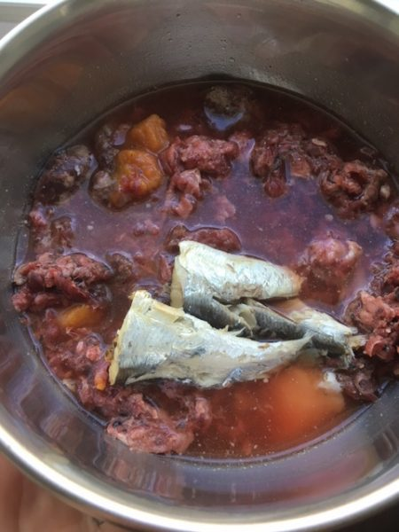 Raw dog food topped off with canned sardines in water