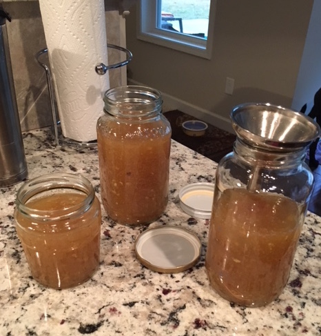 Pouring Bone Broth Into Mason Jars For Storage