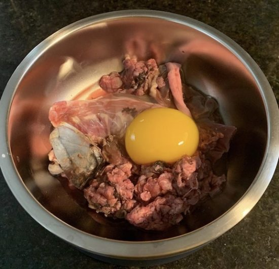 K9sOverCoffee.com | Raw dog food featuring a duck egg and half a duck neck